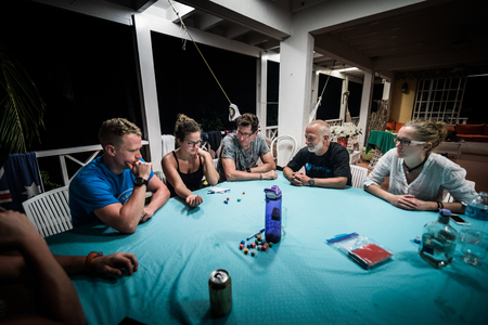 SAN ANDRES ISLAND, Colombia _ Circa March 2017. Group of Adults playing Yum Dice Game at Night on the Balcony.