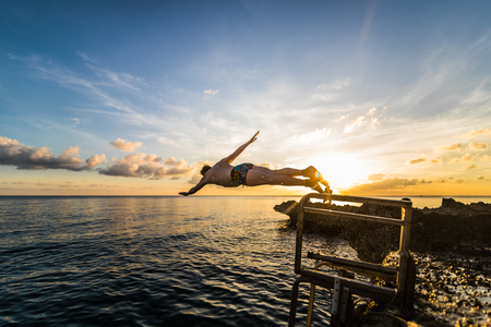 SAN ANDRES ISLAND, Colombia _ Circa March 2017. Person Jumping down a little Volcanic Rock Cliff into the Caribbean Sea of San Andres during a Beautiful Sunset.