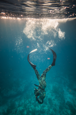 SAN ANDRES ISLAND, Colombia _ Circa March 2017. Amazing Light and Perfect Duck Dive into Water Performed by Freediver in the Cristal Clear Caribbean Ocean