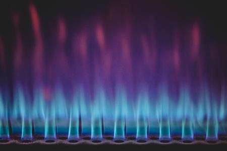 Vista de lenguas de fuego ardiendo en llamas y calentando el cilindro tostador para tostar café