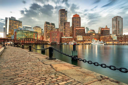 Downtown skyline city view of Boston Massachusetts USA looking over the riverfront harbor and marina boat dock from Fan Pier Park at night
