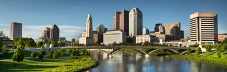 Downtown cityscape panoramic looking over the Scioto River and the Discovery Bridge along the Riverfront Park in the city of Columbus Ohio USA