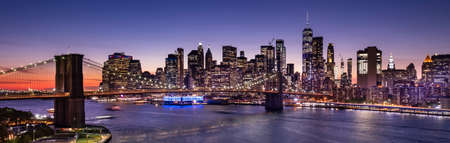 Brooklyn Bridge over the East River and the Manhattan downtown city panoramic skyline at night in New York USA