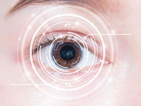 high tech world: Close-up of womans brown eye. High technology in the futuristic. scan, contact lens Stock Photo