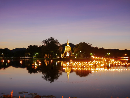 light in Buddha Statue at Temple in Loy Kratong Festival at twilight time, Sukhothai Historical park , Thailand