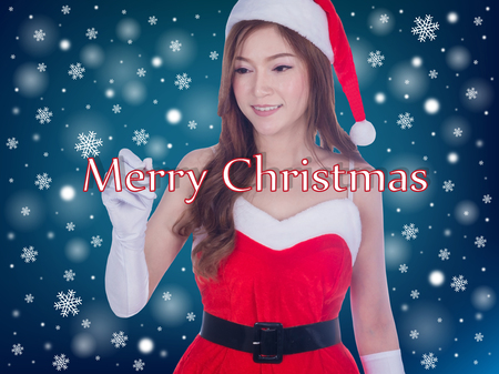 Christmas woman smiling writing merry christmas on screen. Cute beautiful Caucasian santa girl isolated on blue background Banco de Imagens