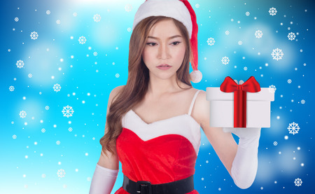 Christmas woman holding christmas gifts smiling. Cute beautiful Caucasian santa girl isolated on blue background Banco de Imagens
