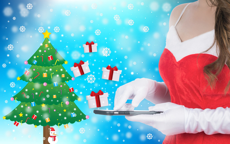 Christmas woman holding smart phone sent christmas gifts on winter background of blue color, christmas holiday concept