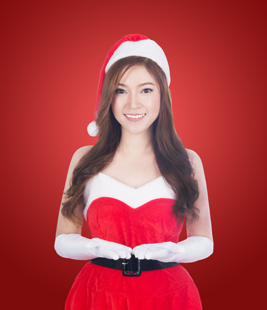 Christmas woman holding Something smiling. Cute beautiful Caucasian santa girl isolated on red background