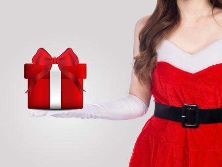 Santa girl holding christmas gift on gray background, christmas holiday concept