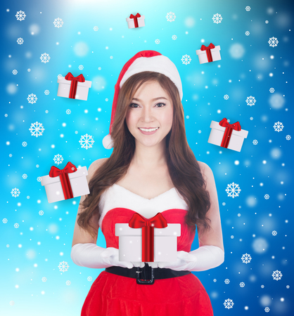 Christmas woman holding Something smiling. Cute beautiful Caucasian santa girl isolated on blue background