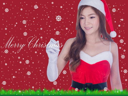 Christmas woman smiling writing merry christmas on screen. Cute beautiful Caucasian santa girl isolated on red background Banco de Imagens