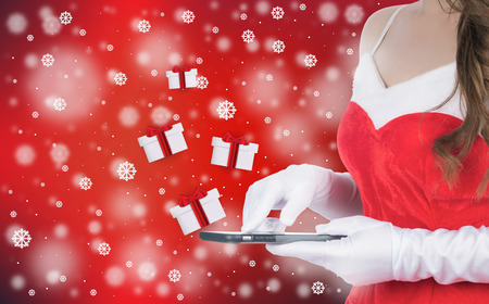 Christmas woman holding smart phone sent christmas gifts on winter background of red color, christmas holiday concept