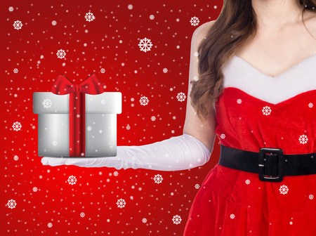 Santa girl holding christmas gift over winter snowflakes background, christmas holiday concept