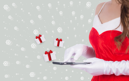 Christmas woman holding smart phone sent christmas gifts on gray background, christmas holiday concept