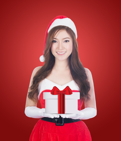 Christmas woman holding christmas gifts smiling. Cute beautiful Caucasian santa girl isolated on red background Banco de Imagens