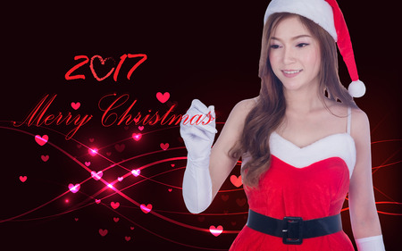 Christmas woman writing merry christmas 2017 on screen with Overlaying wavy lines and hearts abstract. Asian / Caucasian model in Santa