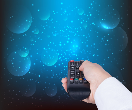 woman holding TV remote control on blue background