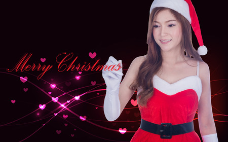Christmas woman writing merry christmas on screen with Overlaying wavy lines and hearts abstract. Asian / Caucasian model in Santa