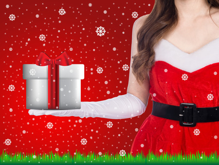 Santa girl holding christmas gift over winter snowflakes background, christmas holiday concept
