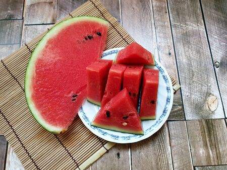 Fresh watermelon slice. Summertime fruit on the bamboo mat and wooden background