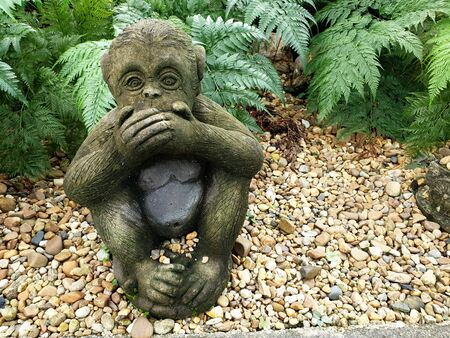 One of three wise monkeys in the garden, Three wise monkeys are a pictorial maxim, embodying the proverbial principle
