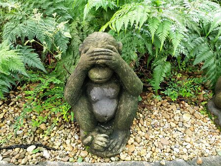One of three wise monkeys in the garden : Three wise monkeys are a pictorial maxim, embodying the proverbial principle