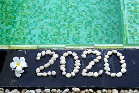 Happy New Year 2020 written by stones on floor tile background close up green swimming pool