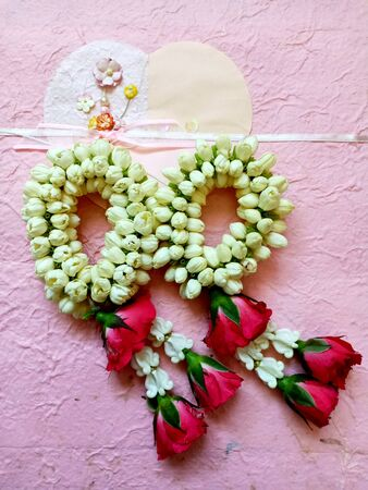 Jasmine garland on pink mulberry paper background, made of rose and Jasmine flowers use for special days, such as Songkran day, Loy Krathong, Mother day, Wedding, offer the monk or buddha.