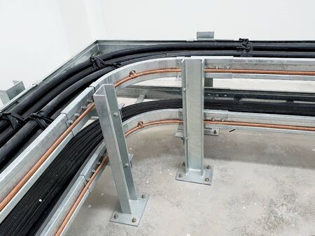 Horizontal bend of cable tray installation in a corner of switchgear room in substation.