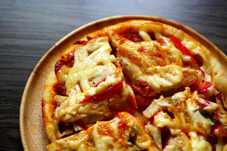 Homemade Hawaiian pizza mozzarella cheese on wooden plate.