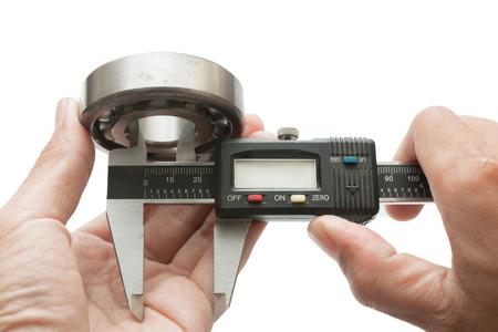 Metal vernier caliper and Ball bearings on white background photo