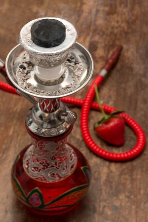 An ornate Syrian sheesha or hooka water pipe on wood table