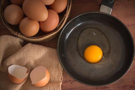 木のテーブルにフライパンで卵の卵と壊れた 写真素材