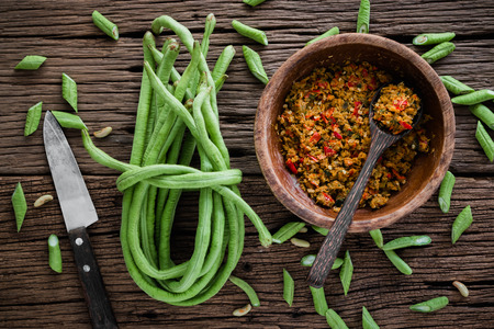 Cowpea or Yardlong bean and thai herbs, spices for stir fry on wood background photo
