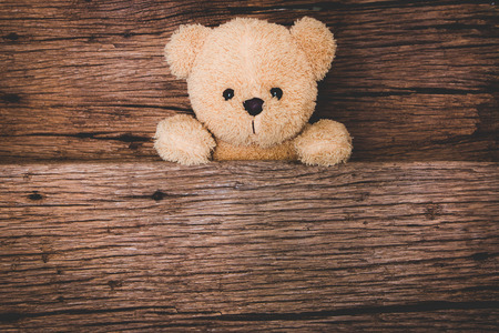 Cute brown teddy bear in old wood background Stock Photo