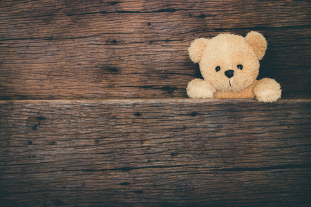 teddy bear background: Cute brown teddy bear in old wood background Stock Photo
