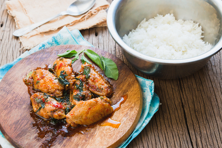 santa cena: pollo frito con hojas de albahaca con arroz jazm�n sobre fondo de madera vieja