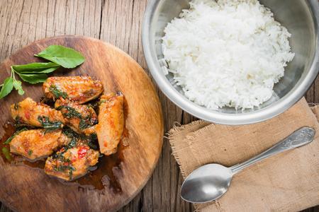 santa cena: pollo frito con hojas de albahaca con arroz jazmín sobre fondo de madera vieja