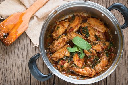 santa cena: pollo frito con hojas de albahaca en crisol en el fondo de madera vieja