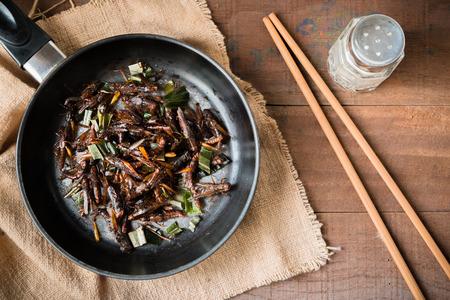 塩、コショウ、醤油とパンダン シーズンと揚げバッタ。古い木製のテーブルの上