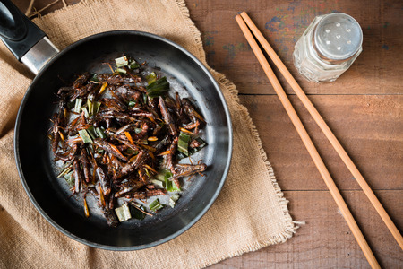 cooking food: Fried grasshopper with pandan Season with salt, pepper and soy sauce. on old wooden table