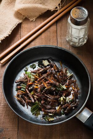 mealworm: Fried grasshopper with pandan Season with salt, pepper and soy sauce. on old wooden table