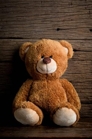 Cute teddy bears sitting on old wood background