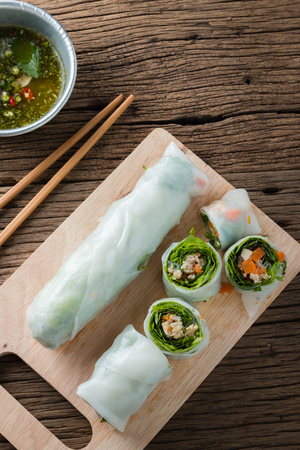 cuon: Fresh Spring Rolls with vegetables and pork on old wooden table