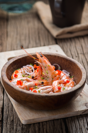 caterers: steamed shrimps in a wooden bowl on wood background