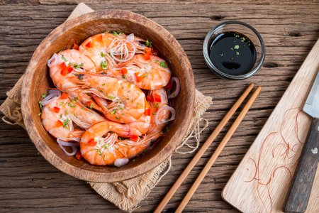 Steamed shrimps in a wooden bowl on wood photo