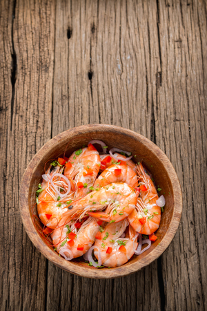 steamed shrimps in a wooden bowl on wood background photo
