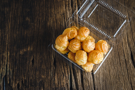 Cream Puffs in Plastic packaging on wooden background.