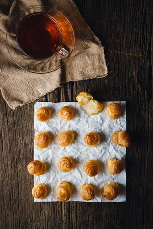 creampuff: Cream Puffs with Black tea on wooden .